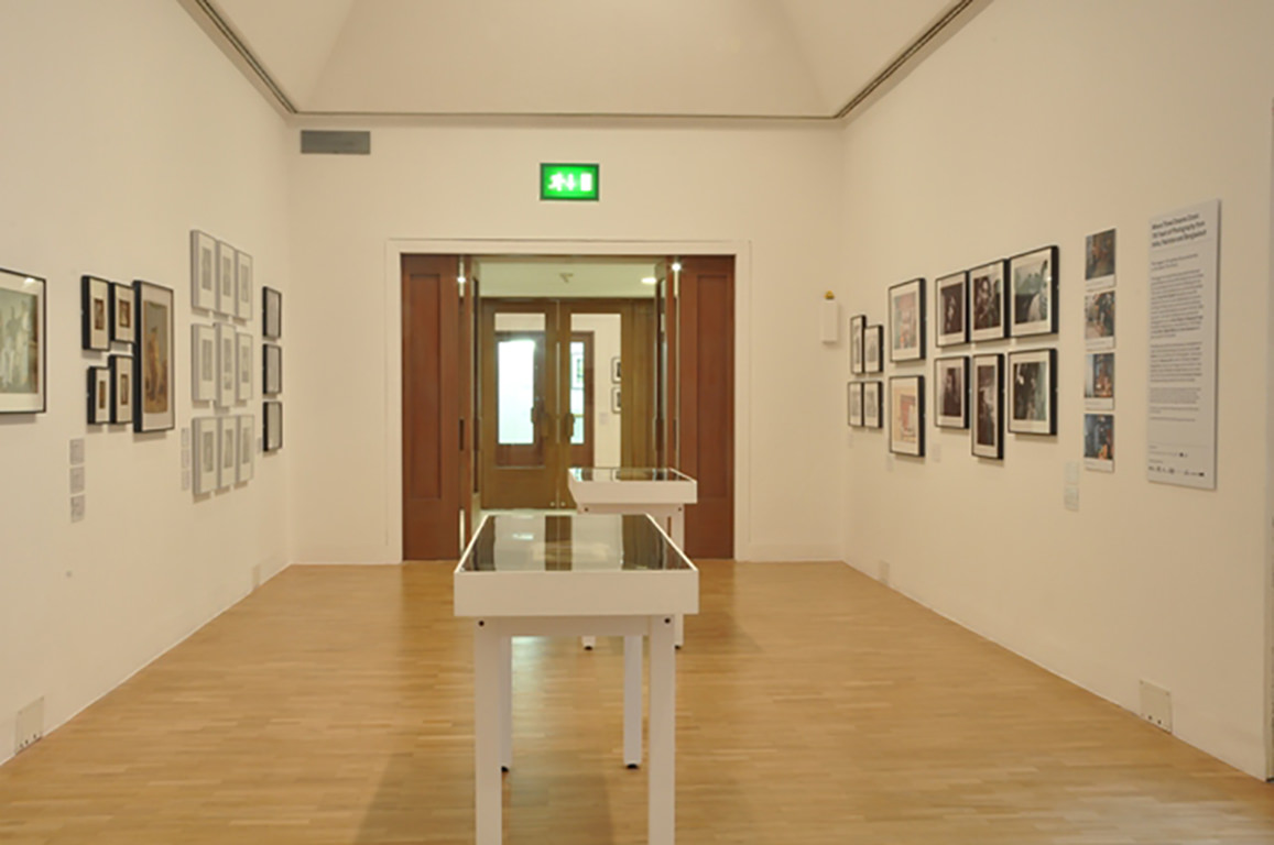 Interior of exhibition with works hung on walls and displayed in vitrines