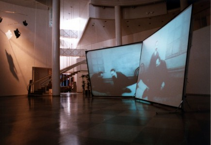 Ashiya City Museum of Art & History, video installation with two screens, 300 x 400 cm each; and (left) Sarah Lucas, <i>Me Suspended (second version)</i>, 1993, PVC photocopies, poles, and wire