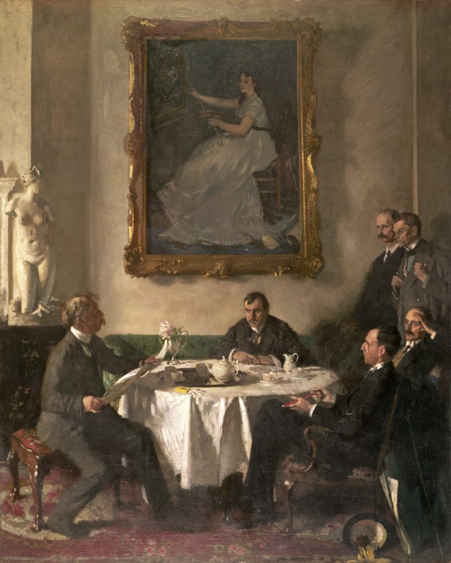 Group of men sat at table in front of large painting of woman