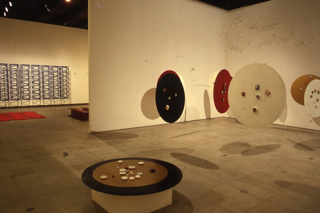 Circular forms hung from ceiling of interior space and placed on floor, with wall-mounted sculpture in background