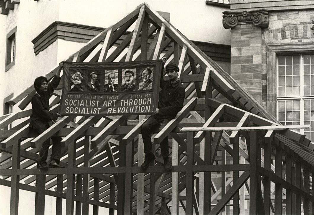 Two men sat on building frame holding banner advocating for Socialism