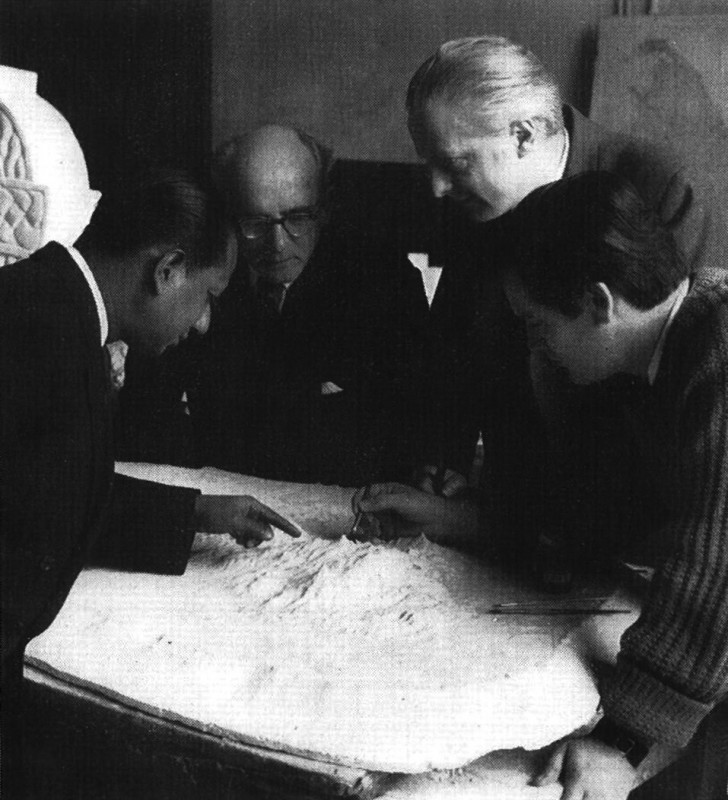 Suited men peer over a white relief model